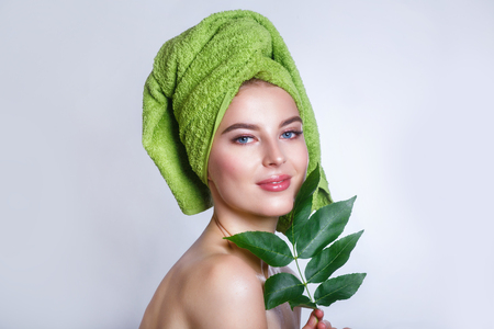 woman with a green towel on her head .Beautiful woman face portrait with green leaf , concept for skin care or organic cosmetics