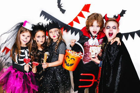 Children in halloween costumes show funny faces Imagens