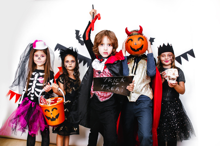 Halloween party. Funny kids in carnival costumes on white background