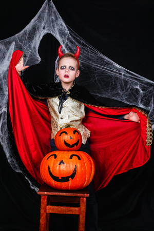 A young boy in halloween devil costume with pumpkins having fun Stock Photo