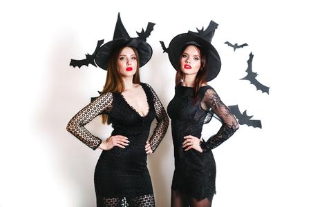 Twee gelukkige sexy vrouwen in zwarte heksenhalloween-kostuums op partij over witte achtergrond