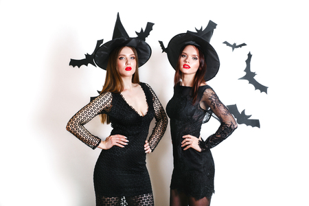 Two happy sexy women in black witch halloween costumes on party over white background