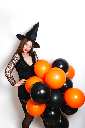 happy sexy women in black witch halloween costumes with orange and black balloon on party over white background
