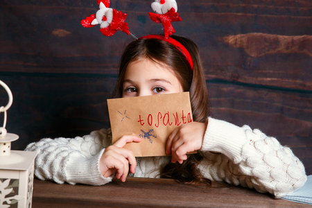 child writes letter to Santa Claus . Funny girl in Santa hat writes letter to Santa