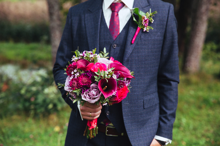 Elegant groom in costume and bow-tie with bouquet .