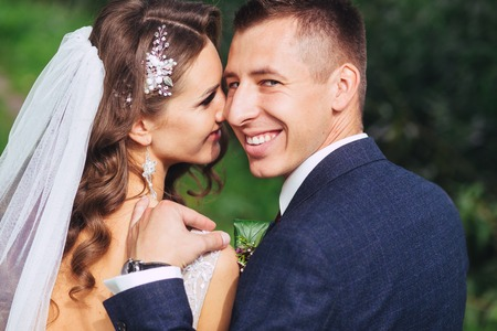 Beautiful newlywed bride and groom in park face closeup Stock Photo