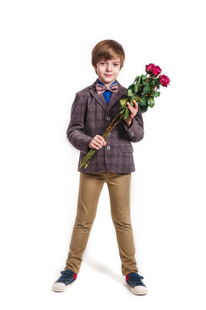 Smiling boy with a bouquet of red roses on white background. Valentine's day, March 8, Mother's Day Фото со стока