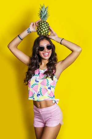 Fashion summer portrait indian girl in sunglasses and pineapple over yellow background