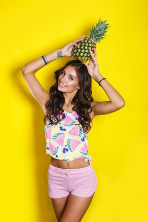 Fashion summer portrait indian girl with pineapple over yellow background