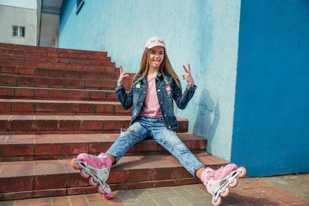 Little pretty girl on roller skates in city 写真素材