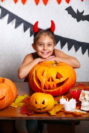 Happy halloween. Funny little child girl with carving pumpkin. Happy family preparing for Halloween.