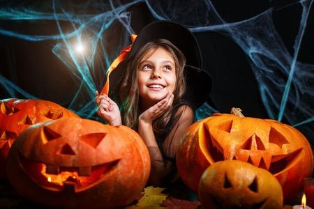 Concepto de Halloween - niño bruja disfruta jugando con varita mágica sobre telaraña y con fondo de calabazas curvas.
