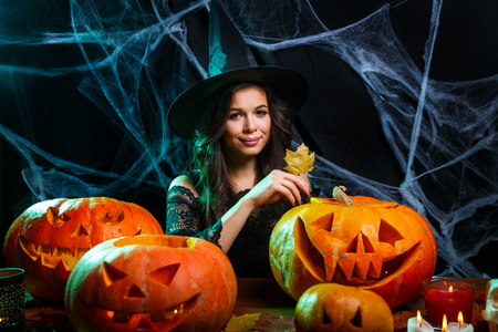 Halloween concept - young woman with halloween sweet and candy with cheerful smiling over spider web and with curved pumpkins background.