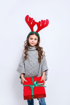 Happy little smiling girl with christmas gift box looking in camera. Christmas concept. Smiling funny girl in deer horns in studio.