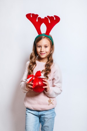 Happy little smiling girl with red Christmas tree ball. Christmas concept. Smiling funny girl in deer horns on white background