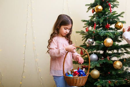 Merry Christmas and Happy Holidays. Cute little child girl is decorating the Christmas tree indoors.