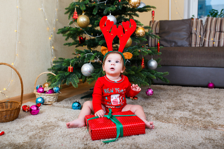 Cute baby reindeer holding Christmas gifts at christmas tree at home room
