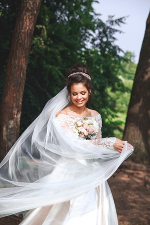 Beautiful bride in fashion wedding dress on natural background. Wedding day. Archivio Fotografico