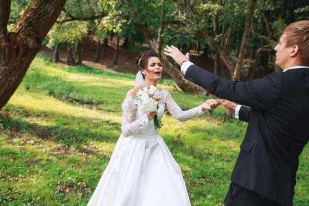 Happy handsome groom and beautiful bride in white dress laughing and dancing in the park Фото со стока