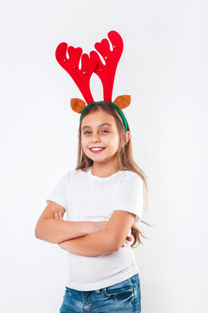 Smiling funny child in deer horns and white t-shirt looking at camera . Stock Photo