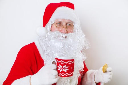 Close up of happy Santa Claus with glass of milk and cookie. Christmas time
