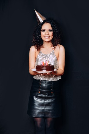 Portrait of a young beautiful brunette girl holding birthday cake with candles on black background