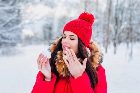 Woman applying moisturizer cream to hydrate skin in winter Stock Photo