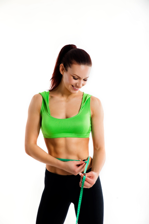 Attractive female bodybuilder measuring her waist with measurement tape. Photo of young woman in sportswear on white background.