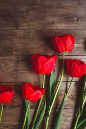 Beautiful red tulips on brown wooden background with space for text. Top view, flat lay.