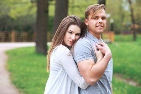 Happy couple expecting pregnancy portrait in park