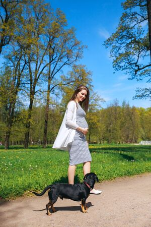 Pregnant young woman touching her big belly and walking in the park