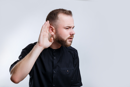 Businessman hold his hand near ear for listening carefully