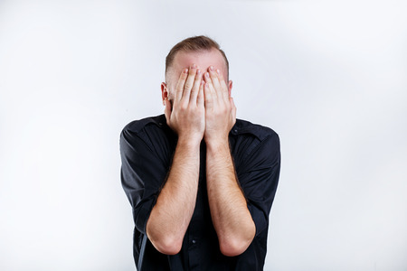 Portrait of man in black shirt closes his eyes with hands Stock Photo