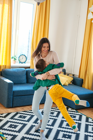 Beautiful woman and her cute little son are playing and smiling at home