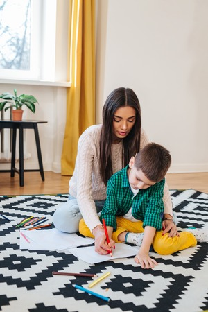 Beautiful woman and her cute little son are drawing and smiling while sitting on the floor at home