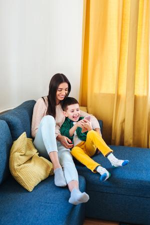 Hermosa joven mamá y su pequeño hijo usando un teléfono inteligente y sonriendo mientras está sentado en el sofá en casa Foto de archivo