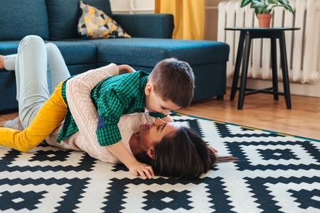 beautiful woman and her cute little son having fun while lying on the floor 版權商用圖片