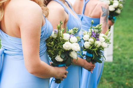 Wedding ceremony flower in hands of bridesmaids