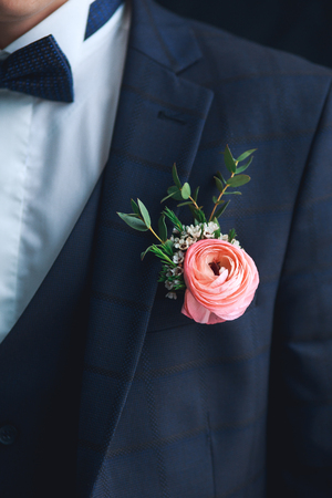 Close-up of pink ranunculus boutonniere on stylish groom