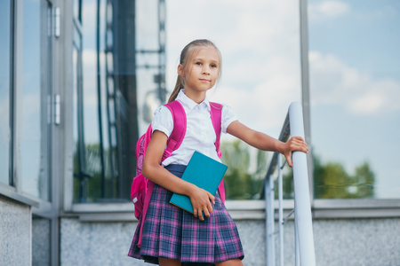Back to school. Portrait of beautiful young schoolgirl with book and backpack, education concept