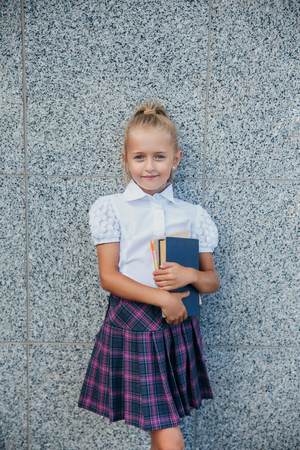 Portrait of a school girl in uniform with book Reklamní fotografie
