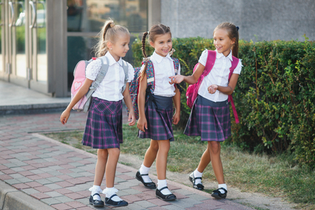 Happy school children in uniform and with backpacks holding hands and jumping in the park, back to school. School holidays Reklamní fotografie