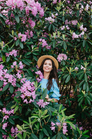 Portrait of young beautiful woman in straw hat posing among blooming Rhododendron trees