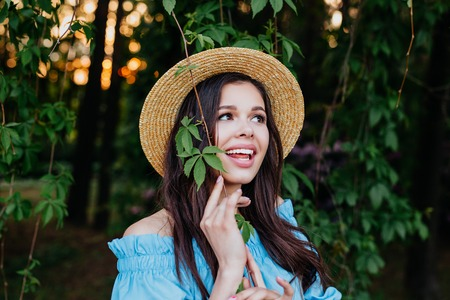 Portrait of pretty young woman in hat standing near leaves outdoors