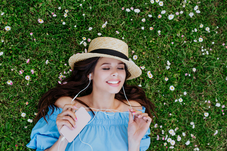 Beautiful woman in hat listening to music with headphones and lying in a garden of white flowers