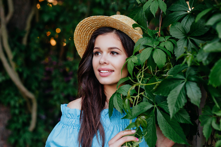 Beautiful woman brunette outdoors. Perfect girl in hat on green leaves background Reklamní fotografie