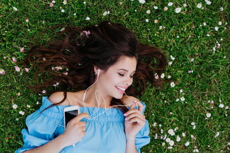 Beautiful woman listening to music with headphones and lying in a garden of white flowers