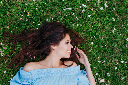 Beautiful young brunette girl in blue dress looking away and lying on a clearing among white flowers