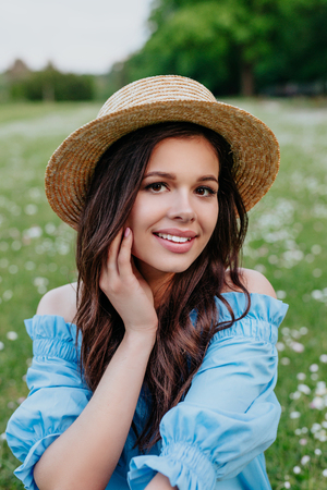 beautiful young brunette woman in straw hat on the meadow with white flowers on a warm sunny summer day Reklamní fotografie