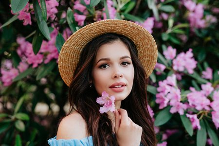 Close up potrait of beautiful young brunette woman in straw hat with pink flowers near her face. Beauty and flowers concept Reklamní fotografie